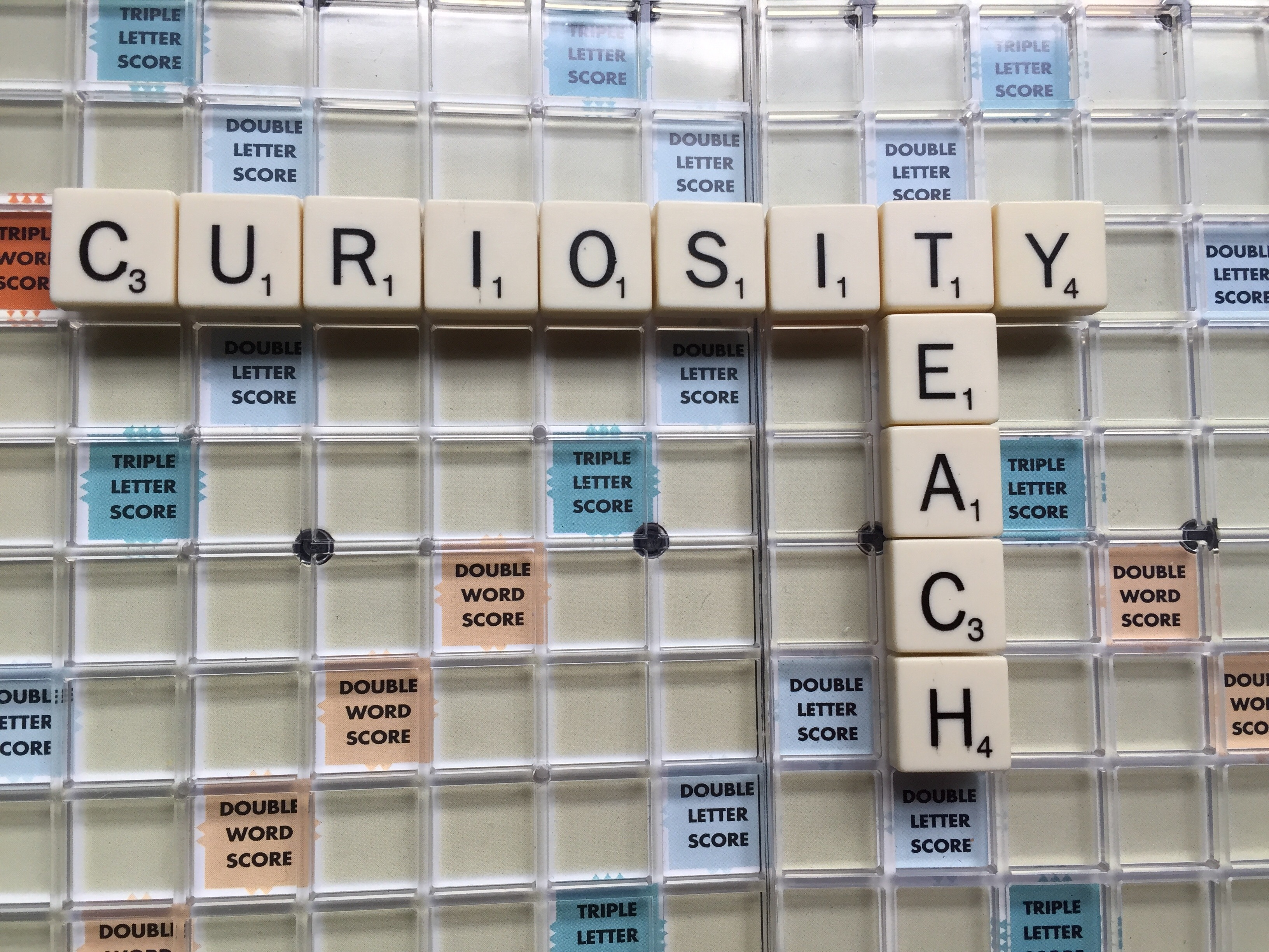 A Scrabble Board with the word Curiosity and Teach
